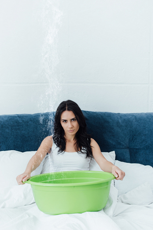 Dissatisfied woman in bed dealing with water damage 写真素材
