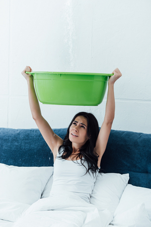 Stressed woman with basin dealing with water damage in bedroom