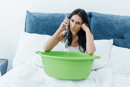 Irritated brunette woman talking on smartphone while sitting in bed with basin Imagens