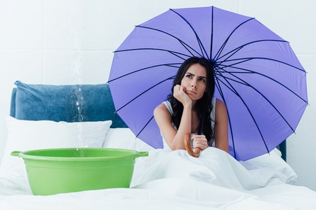 Pensive woman sitting under umbrella during leak in bedroom Banco de Imagens