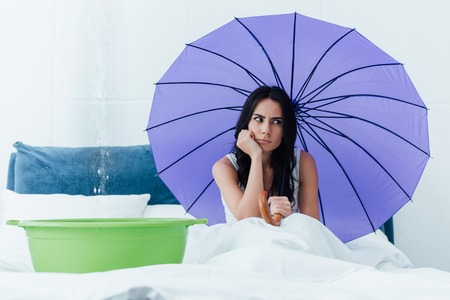 Sad woman sitting in bed with umbrella during water damage