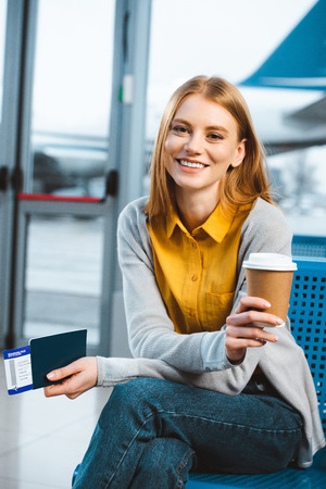 attractive woman smiling while holding disposable cup in airport