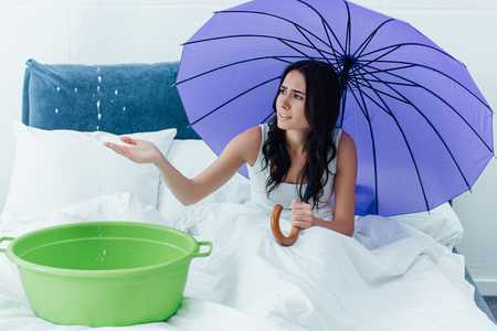 Worried woman with umbrella and basin sitting in bed during leak