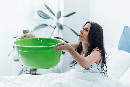 Young woman with green basin dealing with water damage in bedroom
