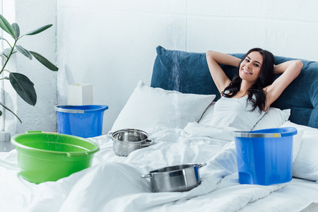Smiling brunette girl in bed dealing with water damage Stock Photo