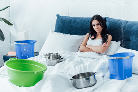Woman lying in bed with crossed arms during water leak