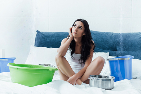 Pensive woman with buckets and pots dealing with water damage in bedroom