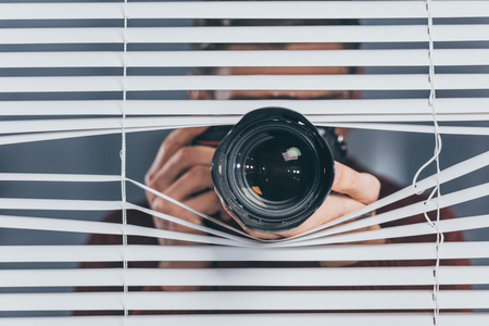 close-up view of young man holding camera and taking pictures through blinds Фото со стока