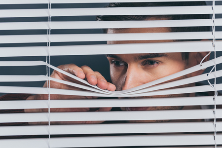 suspicious young man looking away and peeking through blinds
