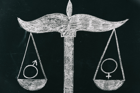 male and female signs on scales drawing on chalkboard, gender equality concept