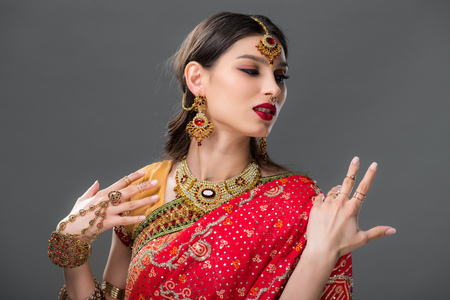 attractive indian woman gesturing in traditional sari, isolated on grey 版權商用圖片