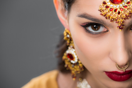 close up of indian woman posing in traditional accessories, isolated on grey Stock Photo - 117464811