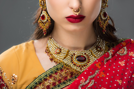 cropped view of indian woman posing in traditional sari and jewelry, isolated on grey
