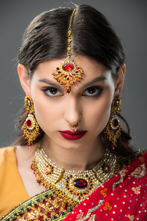 attractive indian girl posing in traditional sari and accessories, isolated on grey