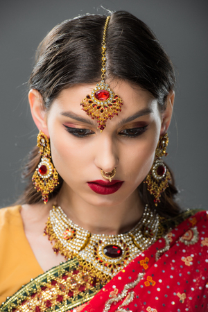 attractive indian woman posing in traditional sari and jewelry, isolated on grey