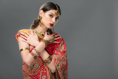 indian girl posing in traditional sari and accessories, isolated on grey