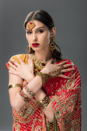 attractive indian woman posing in traditional sari and accessories, isolated on grey
