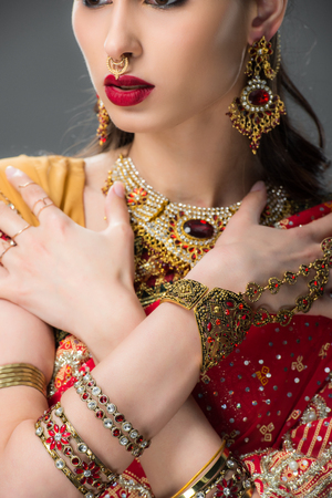 cropped view of indian woman posing in sari and accessories, isolated on grey Stock Photo