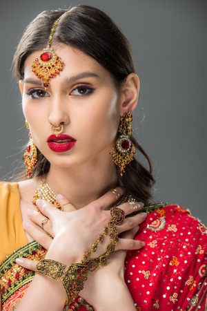 attractive indian woman in sari and accessories, isolated on grey