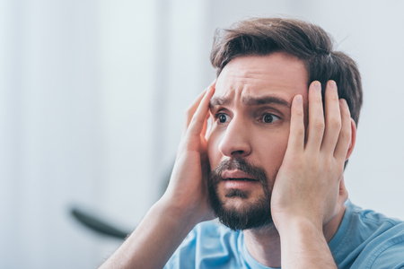 selective focus of frightened man with hands on head and copy space