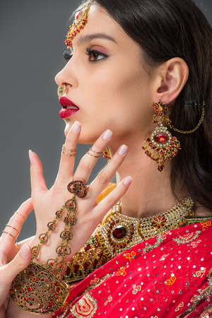 beautiful indian woman gesturing in accessories, isolated on grey 版權商用圖片