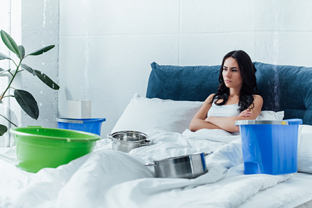 Upset woman lying in bed with pots and buckets