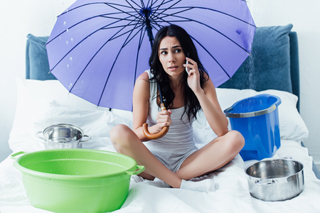 Sad young woman talking on smartphone and holding umbrella in bedroom