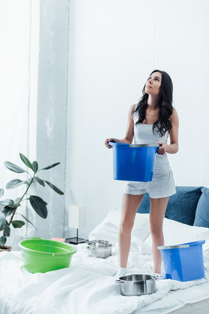 Woman standing on bed with bucket and looking up Imagens