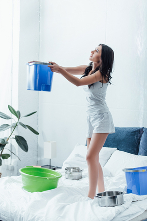 Upset woman standing on bed with bucket and looking at ceiling