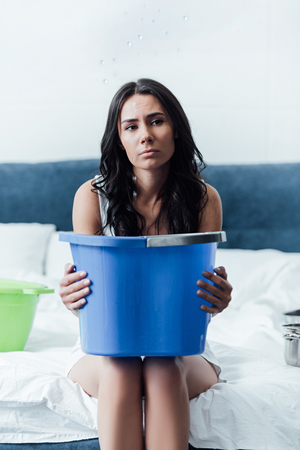Sad brunette woman holding blue bucket in bedroom