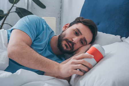 grieving man lying in bed and holding funeral urn Foto de archivo - 117465361