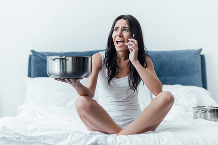 Stressed woman talking on smartphone and holding pot under leaking ceiling