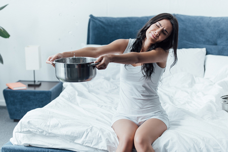 Dissatisfied brunette woman holding pot under leaking ceiling in bedroom