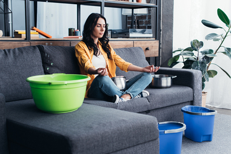Woman sitting in yoga pose during water damage in living room