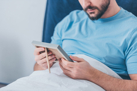 cropped view of bearded man looking at photo frame in bed