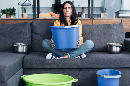Tired woman sitting on sofa with big blue bucket Imagens