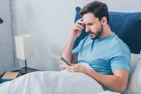 upset man lying in bed and holding photo frame at home