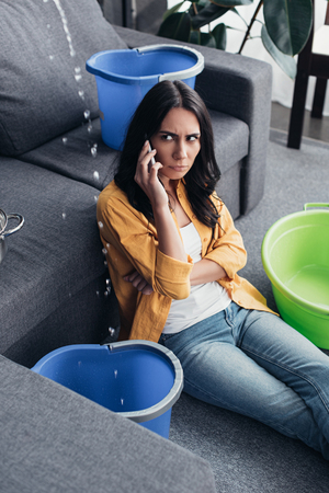 Uspet woman with smartphone looking at water drops in living room