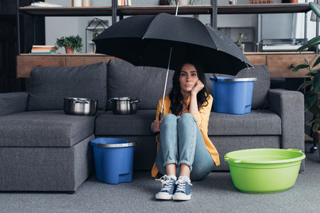 Nadenkend brunette meisje zittend op de vloer met paraplu