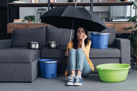 Pensive brunette girl sitting on floor with umbrella