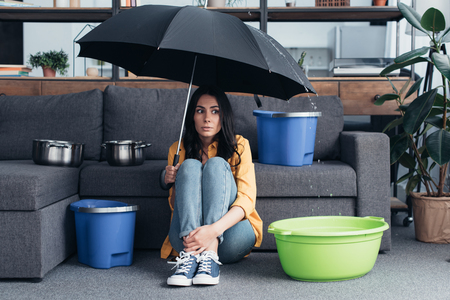Confused girl sitting under umbrella in living room Imagens