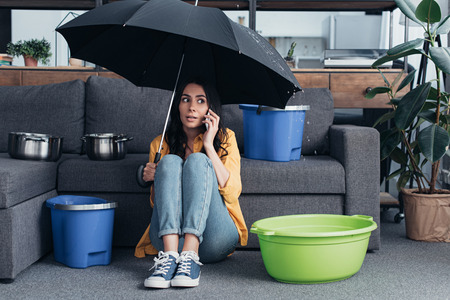 Girl in jeans sitting in living room with umbrella and talking on smartphone