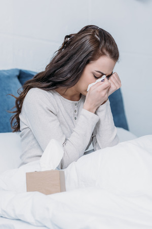 woman lying in bed with tissue box, crying and wiping tears Stock Photo