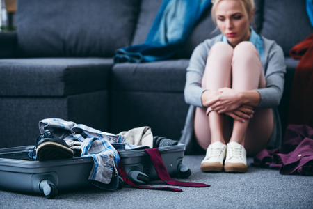 sad woman sitting with scattered clothes and suitcase after breaking up with boyfriend Stock Photo