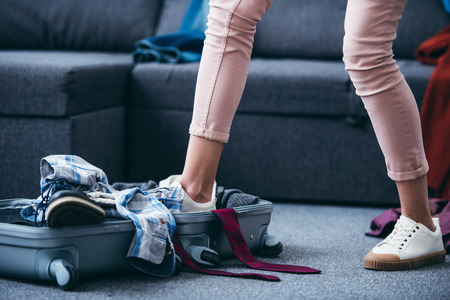 cropped view of woman pushing clothes in suitcase with leg after breaking up with boyfriend