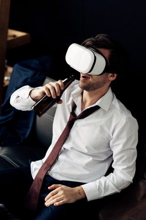 man wearing virtual reality headset and drinking beer