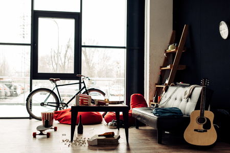 coffee table with food and drinks near sofa and acoustic guitar in messy living room 免版税图像