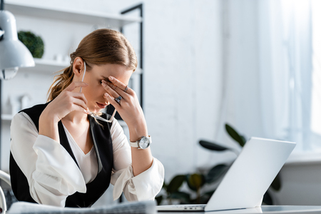 businesswoman in formal wear sitting at computer desk, touching forehead and suffering from headache at workplace Stock Photo