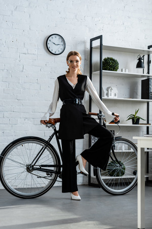 smiling woman in black formal wear with bicycle looking at camera at workplace