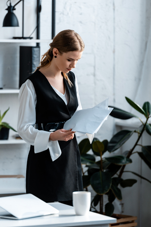 focused businesswoman in formal wear holding documents at workplace Imagens